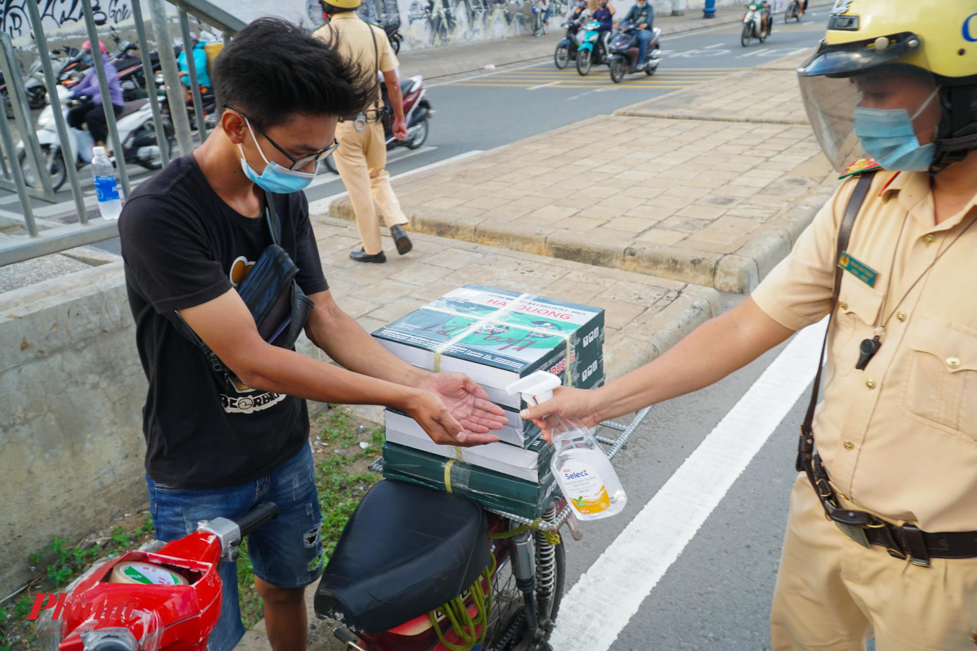 Trước khi làm việc, lượt lượng CSGT tiến hành xịt khử khuẩn tay cho người đièu khiển phương tiện