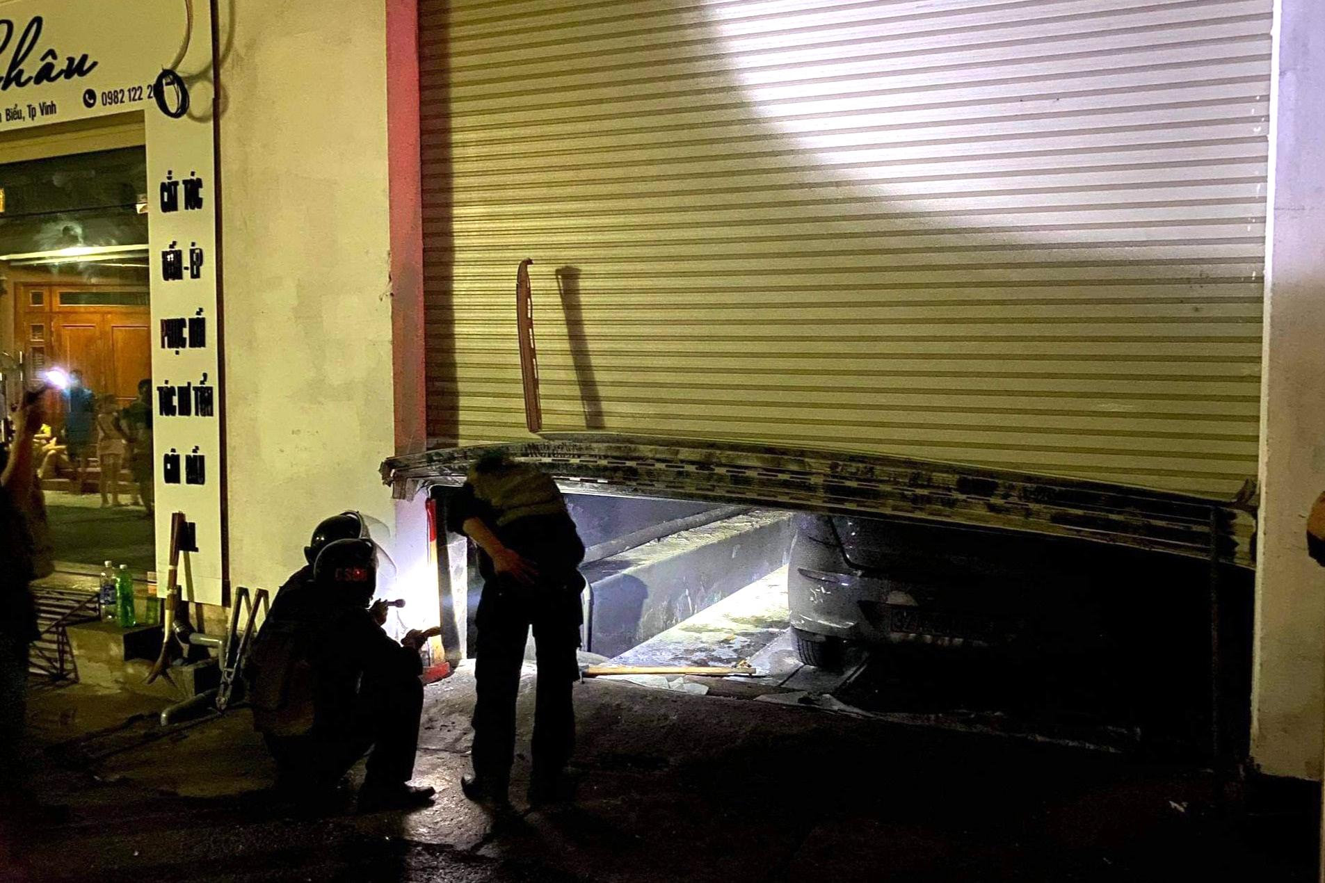 Lực lượng chức năng phá cửa cuốn để dập lửa