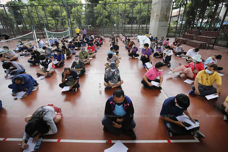 Mọi người ngồi cách nhau trên sàn khi các y tá kiểm tra các hình thức y tế của họ trước khi Covid-19 làm chứng tại sân thể thao PAT ở quận Ratchathewi, Bangkok, vào thứ Ba. (Ảnh: Wichan Charoenkiatpakul)