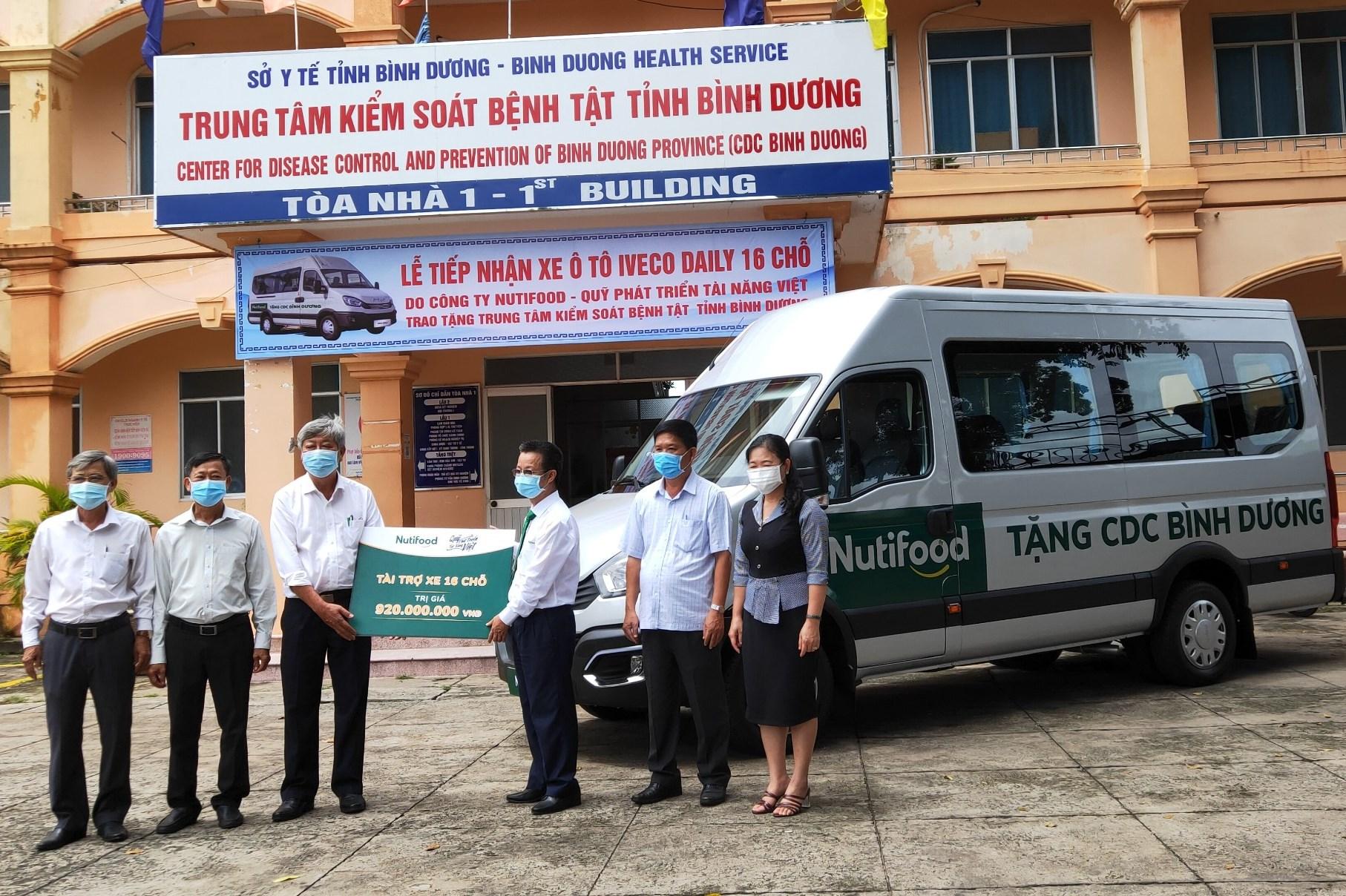 Đại diện Quỹ Phát triển tài năng Việt của Ông Bầu trao xe ô tô 16 chỗ cho Trung tâm Kiểm soát bệnh tật tỉnh Bình Dương. Ảnh: Nutifood