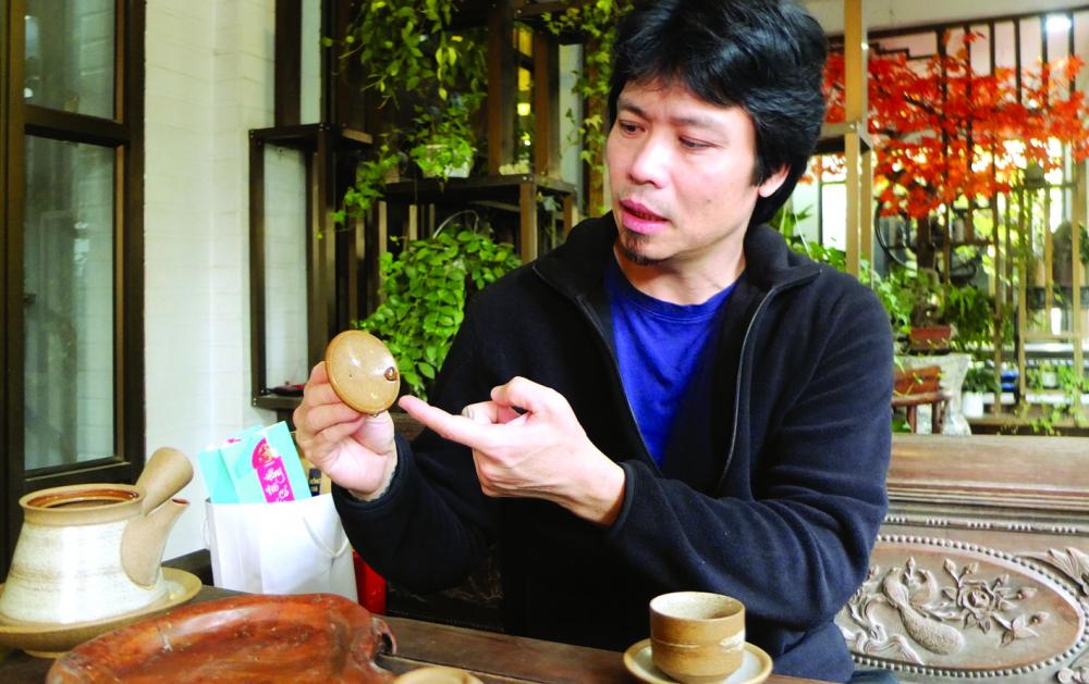 Nghệ nhân Phạm Thế Anh giới thiệu kỹ thuật làm chiếc nắp vừa khít với thân ấm Hồng sa