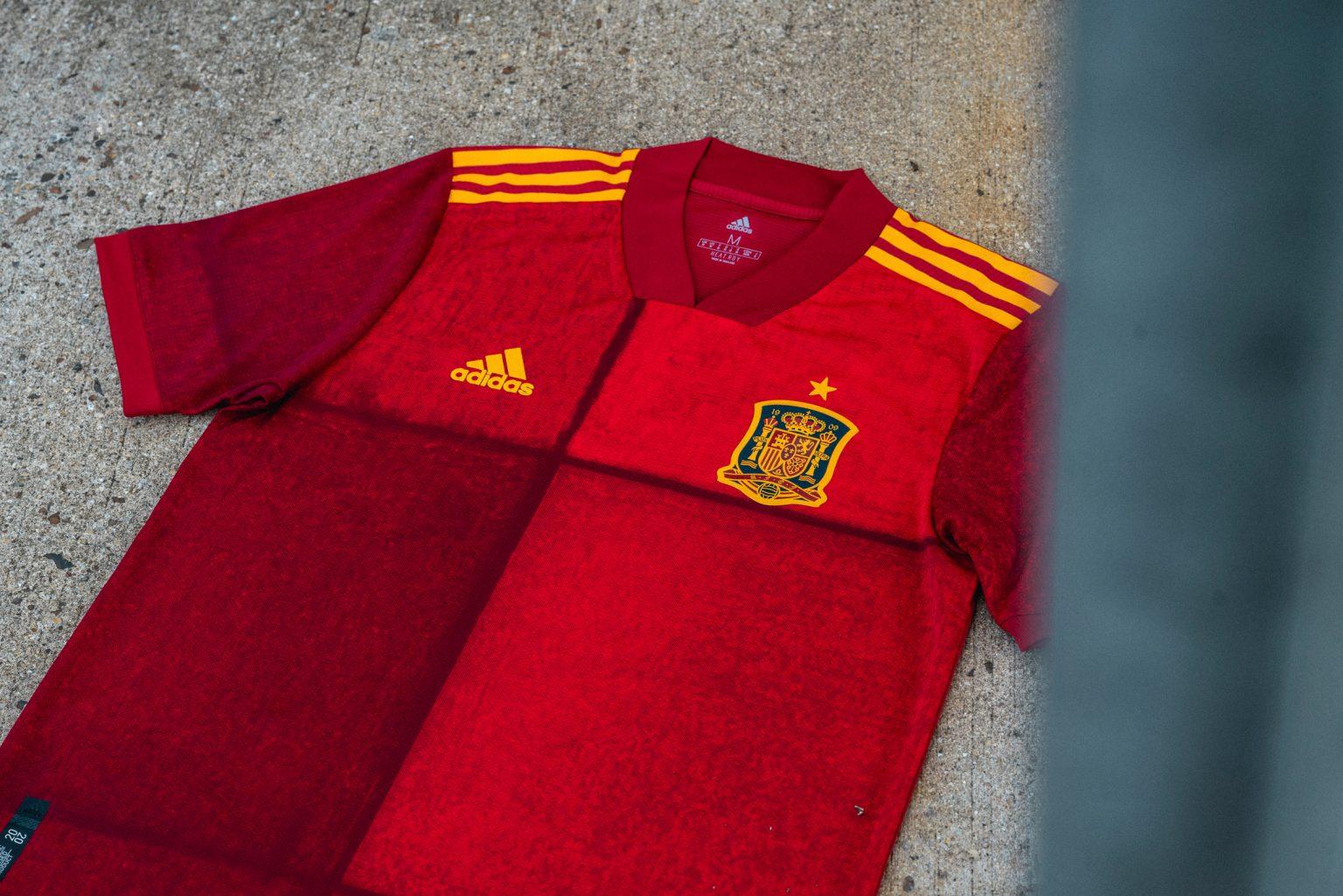 Áo đấu của đội tuyển Tây Ban Nha được adidas thiết kế đặc biệt hơn để kỷ niệm 100 năm thành lập Liên đoàn Bóng đá Tây Ban Nha.  Chiếc áo có các màu sắc pha trộn giữa màu đỏ đậm và đỏ tía có vẻ như chia mặt trước của bộ quần áo mảng màu mang lại hiệu ứng thị giác cho người nhìn.