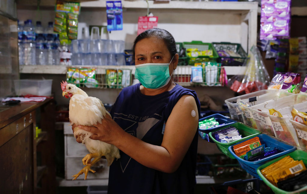 Một phụ nữ 62 tuổi vui mừng vì được tặng gà sau khi tiêm vắc xin COVID-19 - Ảnh: Reuters