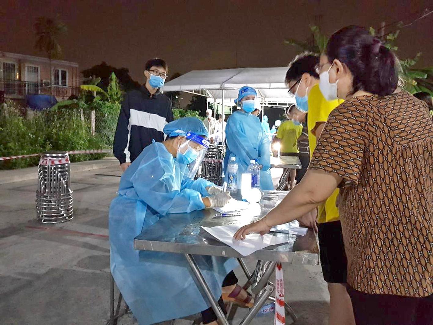 Chị Nuyễn Thị Hồng Tươi - Phó Chủ tịch Hội LHPN P.Thạnh Lộc, Q.12 (ngồi) hỗ trợ công tác lấy mẫu  xét nghiệm COVID-19 cho người dân trên địa bàn
