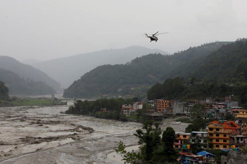 Một máy bay trực thăng của quân đội Nepal làm nhiệm vụ cứu hộ ở Sindhupalchok đang bay trên dòng sông Melamchi nước lũ tràn bờ - Ảnh: Reuters