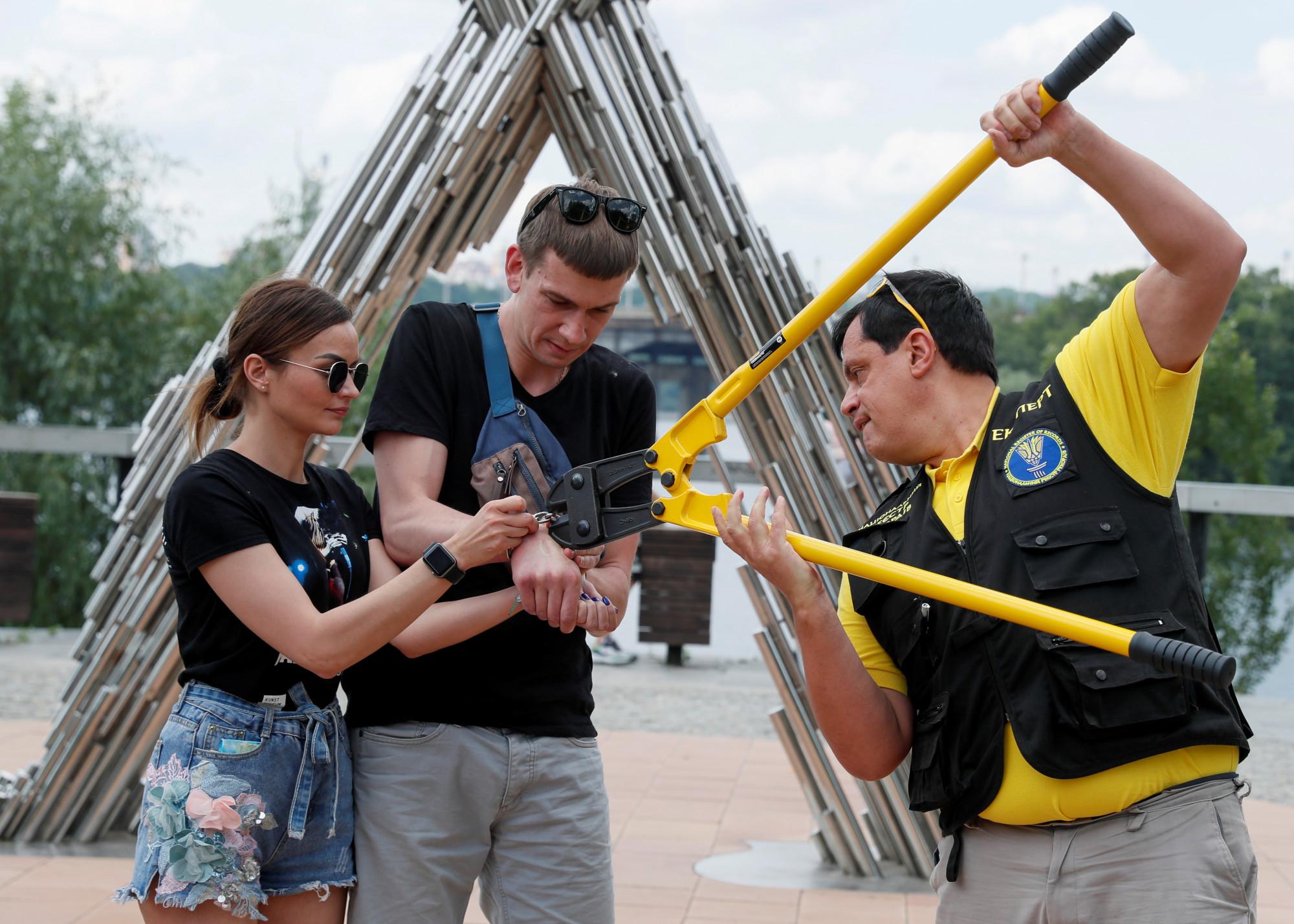 Sau 123 ngày bên nhau cùng chiếc còng trên tay, cặp đôi này đã quyết định phá còng để giải thoát cho nhau - Ảnh: Gleb Garanich /Reuters