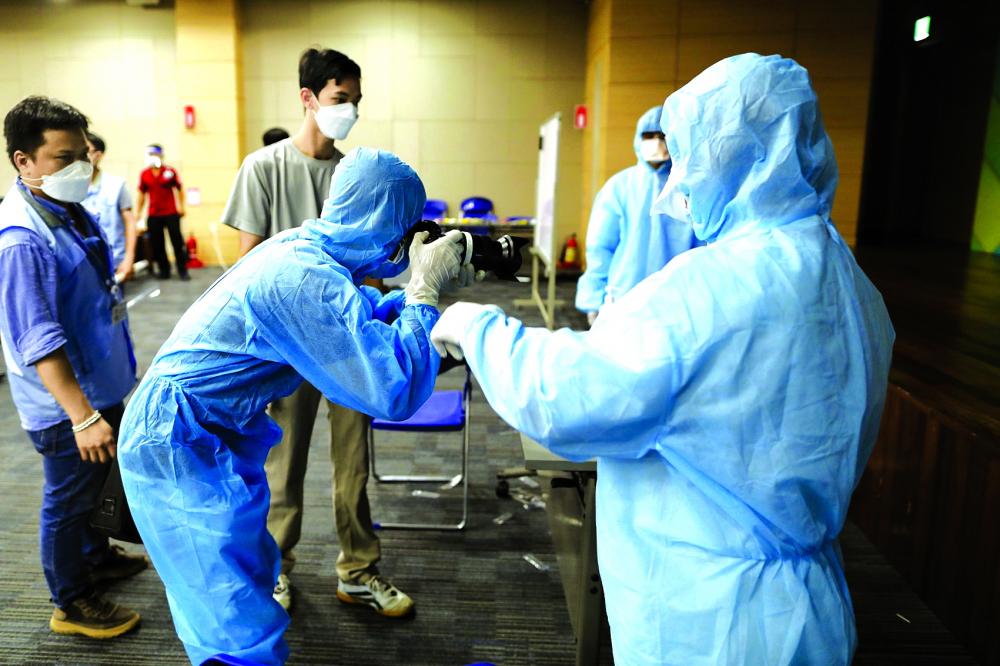 Trước khi vào tác nghiệp ở những khu vực cách ly chống dịch COVID-19, phóng viên phải mặc đồ bảo hộ để đảm bảo an toàn