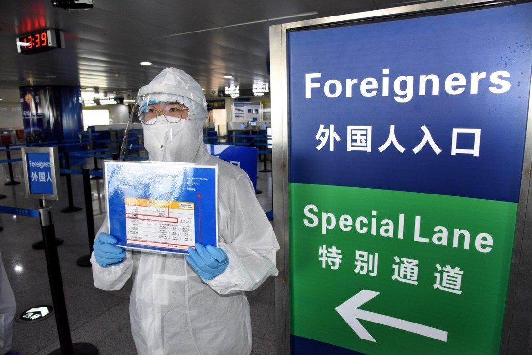 Một nhân viên nhắc du khách nước ngoài điền vào thẻ đến tại sân bay ở Trung Quốc - Ảnh: Xinhua