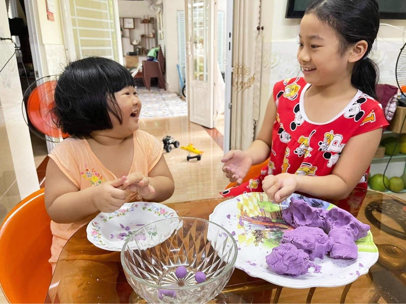 Hai con của anh Nguyễn Trọng Trung (TP.Thủ Đức) học làm bánh, nấu ăn từ khoai lang tím - ẢNH: DƯƠNG BÌNH