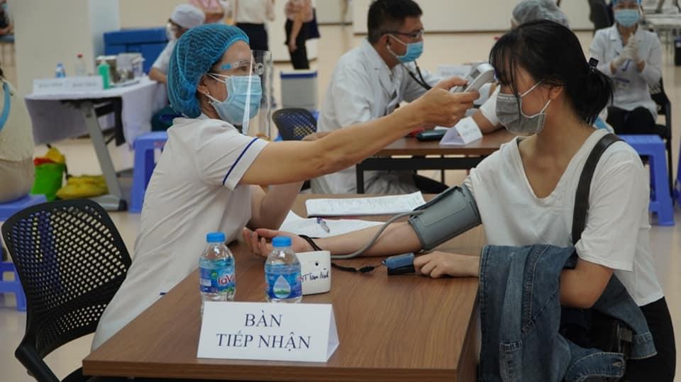 Đo thân nhiệt cho công nhân trước khi tiêm vắc xin ngừa COVID-19 ở quận 7, TPHCM