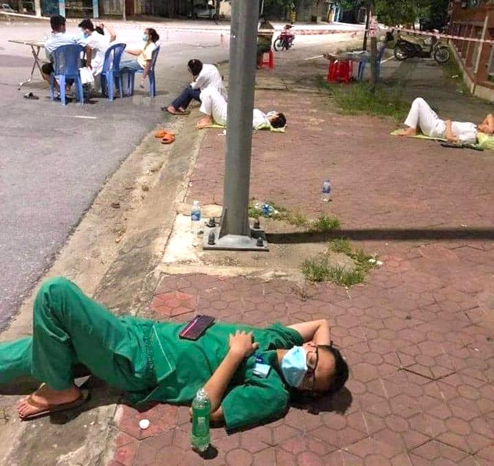 Một số nữ bác sĩ, điều dưỡng nằm chợp mắt trên vỉa hè trong lúc chờ đợi người dân đến lấy mẫu xét nghiệm