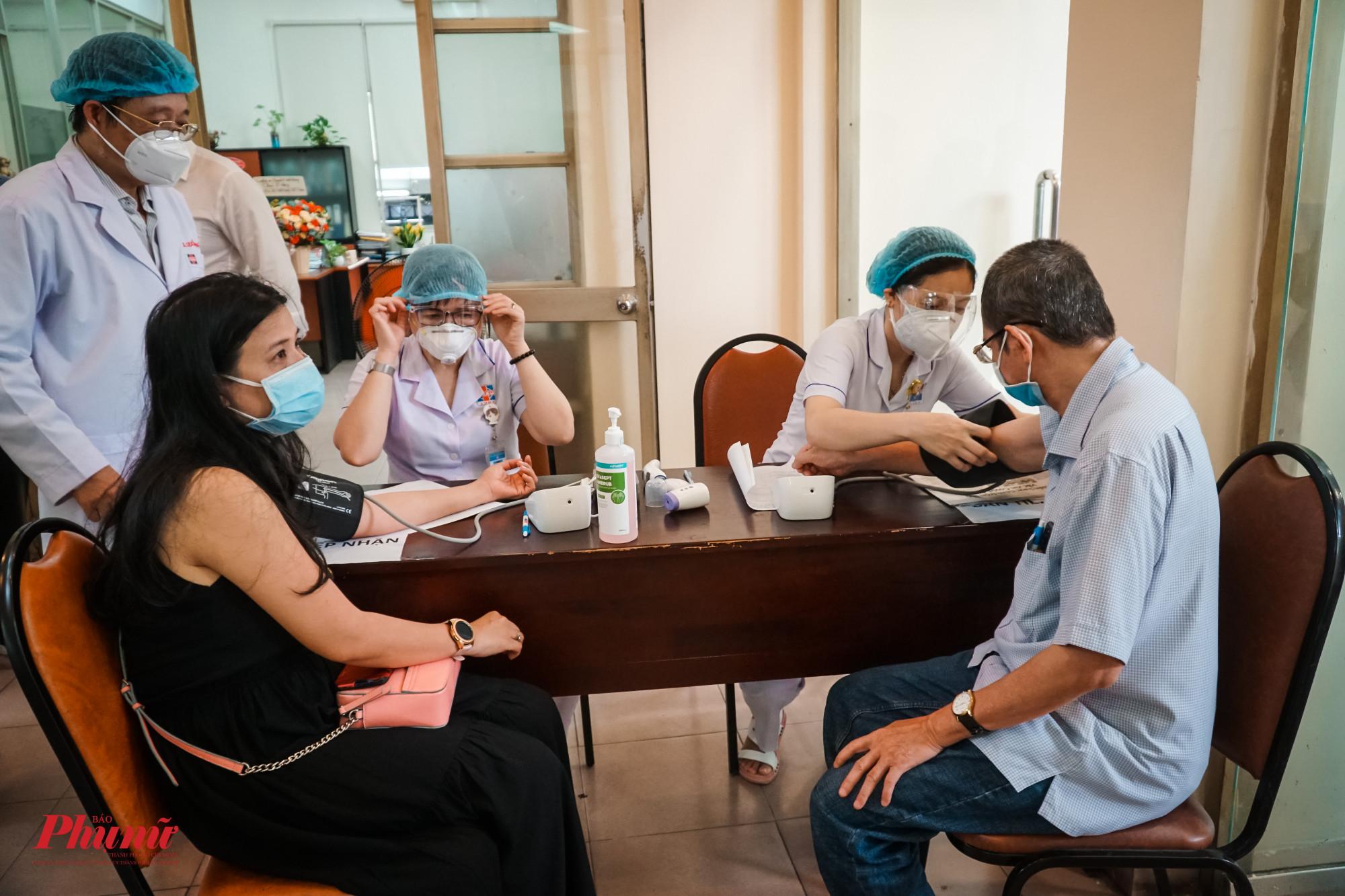 Các phóng viên được đo huyết áp trước khi vào khu vực tiếm chủng