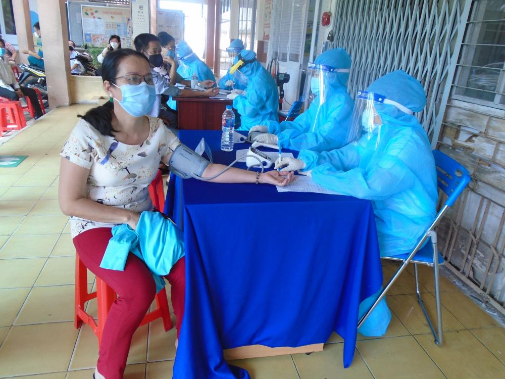 Người dân được đo huyết áp trước khi tiêm vắc xin