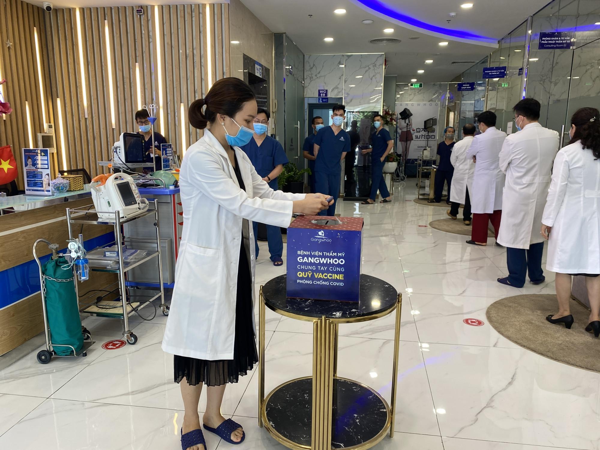 Nhân viên của Bệnh viện thẩm mỹ Gangwhoo xếp thành hàng đợi tới lượt đóng góp cho quỹ vắc xin ngừa COVID-19 của Việt Nam