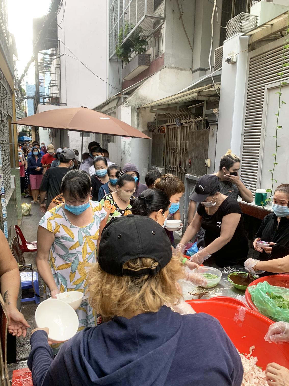 Rất đông người dân xếp hàng nhận các suất ăn do chị Vân phục vụ miễn phí
