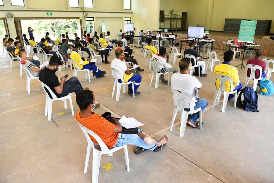 Công nhân nhập cư ngồi chờ tại khu vực theo dõi sau khi tiêm vắc-xin COVID-19  tại Trung tâm tiêm chủng Seletar, Singapore - Ảnh: Straits Times