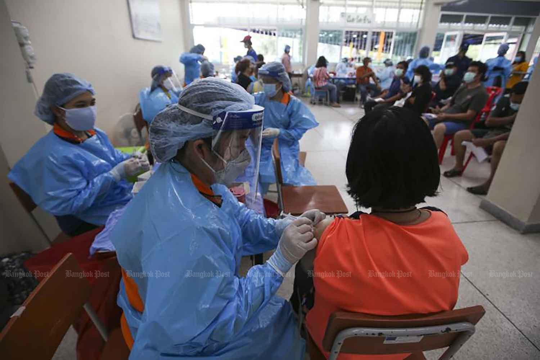 Người dân ở quận Laksi của Bangkok hôm thứ Ba xếp hàng để được tiêm chủng chống lại Covid-19 tại một đơn vị tiêm chủng lưu động ở Trường Bang Khen. Trạm tạm thời, một sự hợp tác giữa Cơ quan Quản lý Đô thị Bangkok và PTT Plc, nhằm giảm tần suất và mức độ nghiêm trọng của các cụm ở thủ đô. (Ảnh: Pattarapong Chatpattarasill)