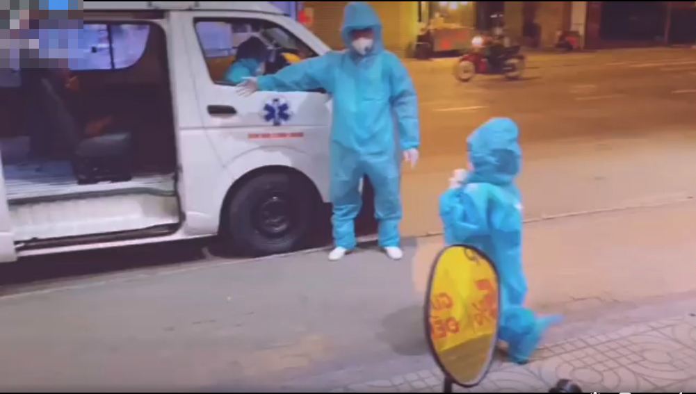 Bé gái trong bộ đồ bảo hộ rộng thùng thình lên xe trong sự hướng dẫn của nhân viên y tế, ảnh cắt từ clip