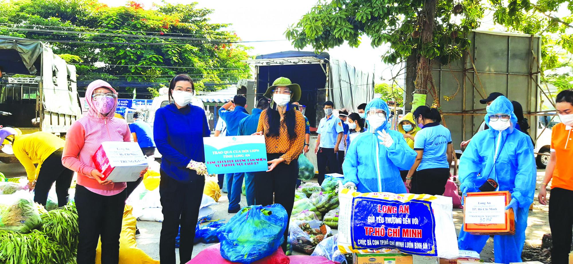 Rau củ và các loại thực phẩm do bà Nguyễn Thụy Thắm (thứ hai từ phải qua) và nhóm bạn ở tỉnh Long An trao tặng người dân TP.HCM