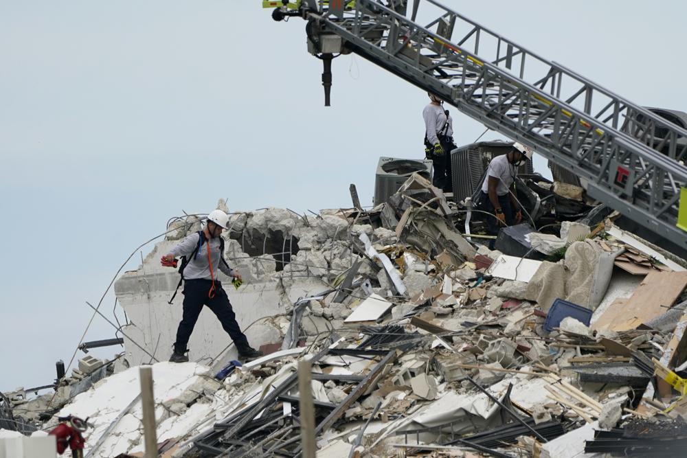 Nhân viên cứu hộ đi bộ giữa đống đổ nát nơi phía cánh của tòa nhà chung cư 12 tầng bên bờ biển đổ sập