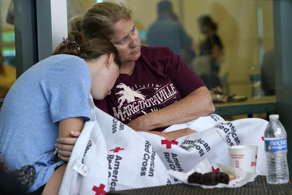 Jennifer Carr (phải) ngồi với con gái khi họ chờ đợi tin tức người thân tại một trung tâm đoàn tụ gia đình