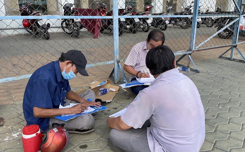 Ở khu vực để xe, nhiều người cũng ngồi trên lề đường, tranh thủ điền thông tin vào phiếu đồng ý tiêm ngừa vắc xin