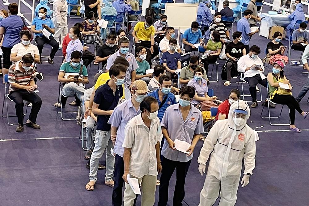 Người dân đủ điều kiện tiêm ngừa được chia thành nhiều nhóm nhỏ, nhân viên y tế sẽ hướng dẫn vào các bàn tiêm