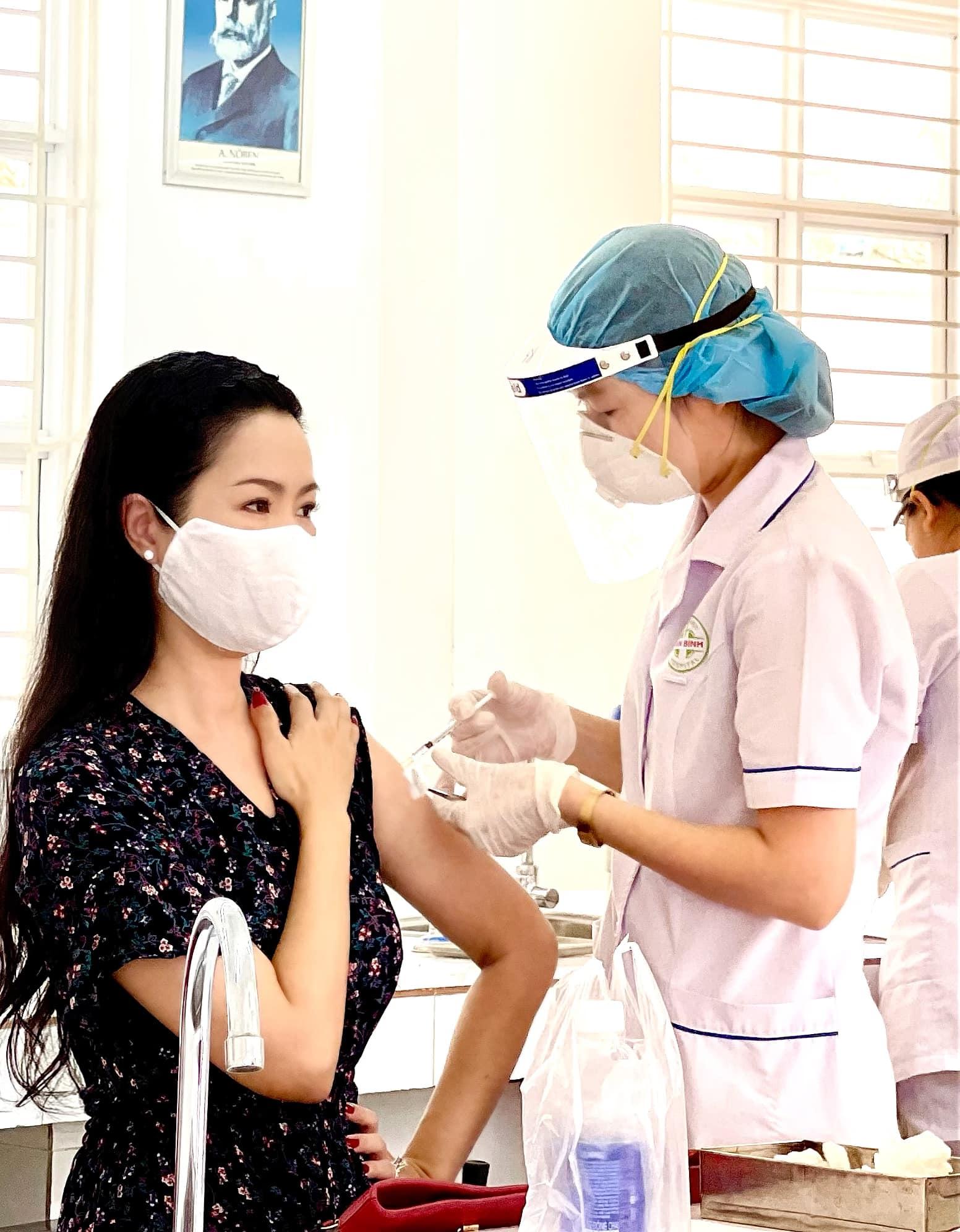 NSƯT Trịnh Kim Chi trong bộ váy tối màu, với phần cánh tay xòe rộng giúp nhân viên y tế dễ dàng tiếp cận vị trí thích hợp để tiêm vắc xin. Nữ nghệ sĩ tâm sự khoảng 6 tiếng sau khi tiêm, cơ thể bắt đầu có cảm giác mỏi cơ, đau đầu, sốt nhẹ giống triệu chứng bị cảm cúm thông thường, không có phản ứng gì đáng ngại.