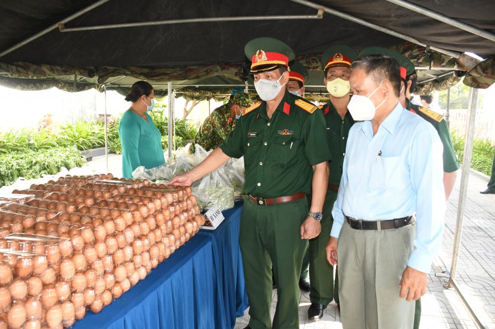 Đại tá Nguyễn Công Anh (thứ 2, từ phải qua) - Phó Chủ nhiệm Chính trị Quân khu 7 - cùng lãnh đạo địa phương kiểm tra công tác chuẩn bị tại các gian hàng trước khi đón người dân tới nhận quà.