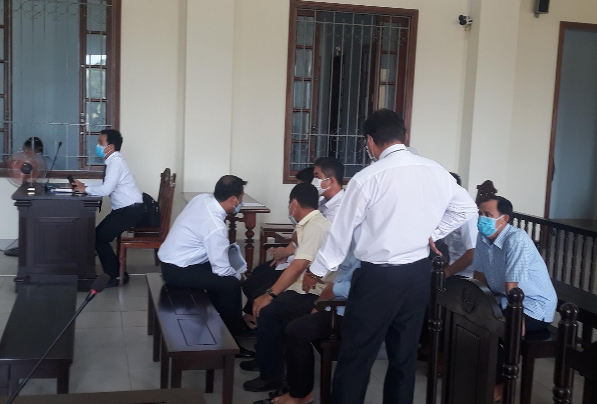 Luật sư và các bị can trao đổi tại phiên tòa