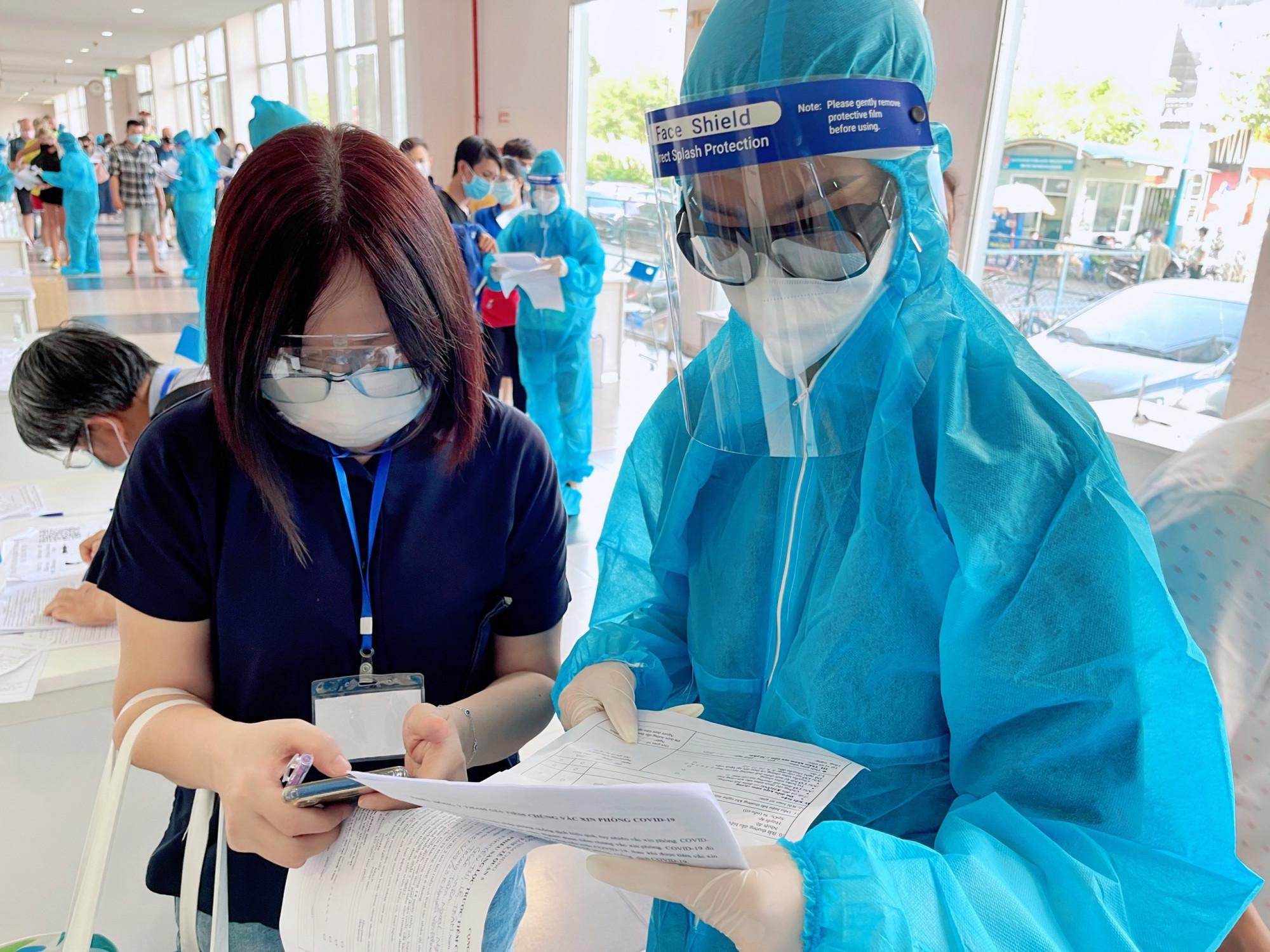 Á hậu Kiều Loan hướng dẫn một người dân khai báo y tế, điền thông tin.