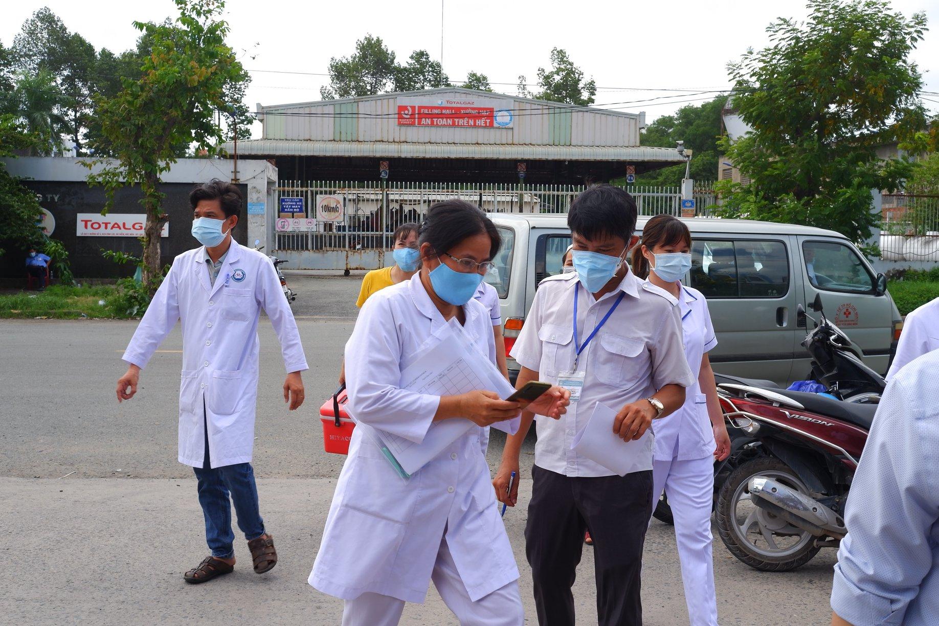 Nhân viên y tế lấy mẫu xét nghiệm cho người tại kho hàng khu công nghiệp Vĩnh Lôc