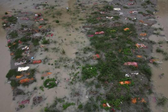 Mực nước dâng cao đã cuốn trôi đất để lộ ra những xác chết được bọc trong vải nghệ tây (Ảnh: AFP)