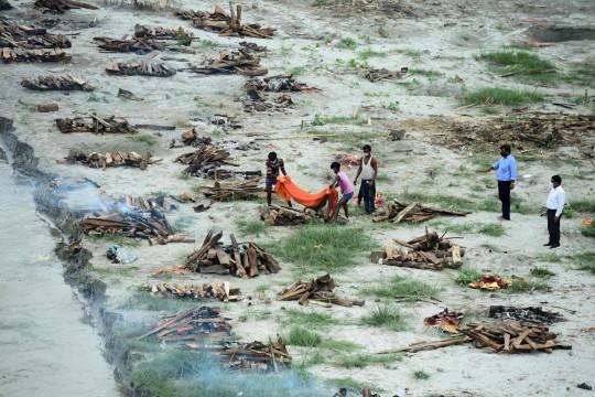 Các công nhân đặc biệt hỏa táng một thi thể được chôn trong một ngôi mộ nông bên bờ sông Hằng (Ảnh: AFP)