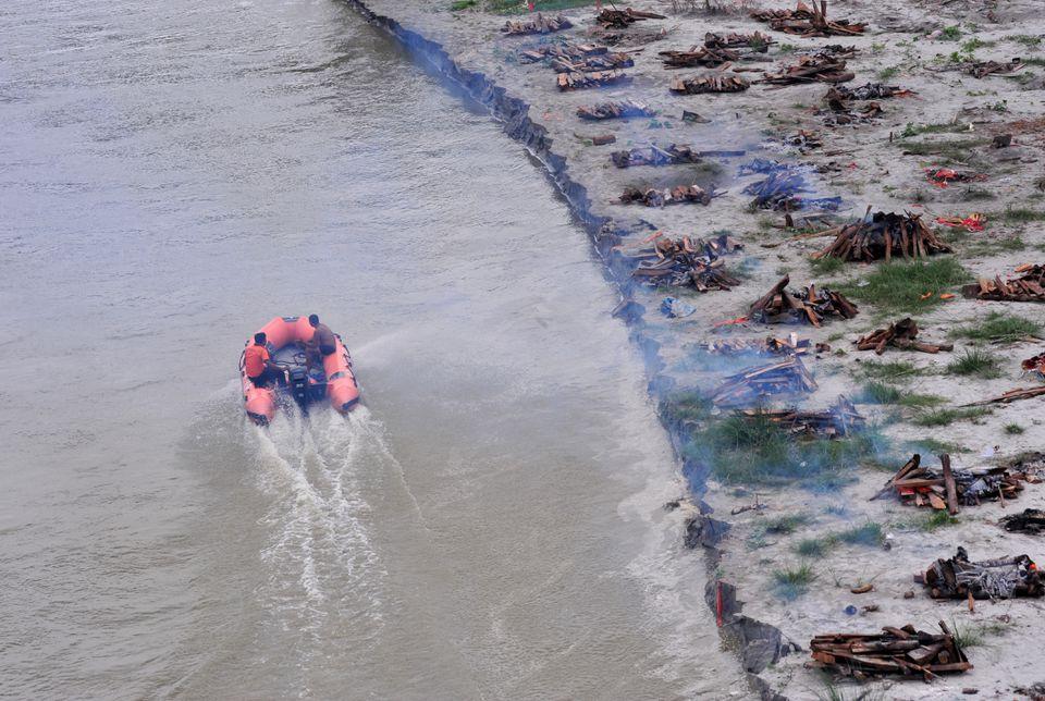 Cảnh sát cùng ngư dân địa phương dùng thuyền để đi vớt xác người trôi trên sông Hằng. (Ảnh AFP)