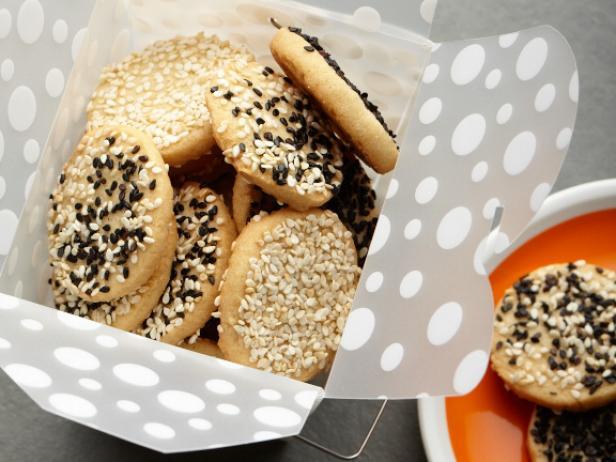 Bánh quy mè  Bạn sẽ cần:  2,5 oz (70 g) bột mì 2 oz (60 g) bơ 4oz (120 g) đường 1 quả trứng 1/2 thìa cà phê chiết xuất vani 1 thìa nước cốt chanh tươi 5,5 oz (160 g) hạt mè 1/2 thìa cà phê bột nở 1/2 thìa cà phê muối Chỉ đường :  Trộn đều bột mì, bột nở và muối. Đánh bông bơ mềm với đường. Thêm trứng, vani và nước cốt chanh vào hỗn hợp. Roi trong 20-30 giây. Ở tốc độ thấp, thêm từng chút bột vào máy trộn Dùng thìa trộn hạt vừng (nhớ rang nhẹ hạt vừng trước).  Làm nóng lò nướng ở nhiệt độ 350F (180 ° C). Cho hỗn hợp lên khay nướng có lót giấy da. Đặt hỗn hợp cookie cách nhau khoảng 3-4 cm vì cookie sẽ lan ra. Nướng 8-15 phút tùy kích cỡ.