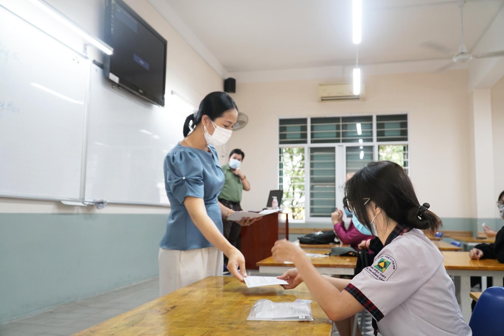 Thí sinh nhận tờ khai báo y tế từ giáo viên - Ảnh: Tam Nguyên