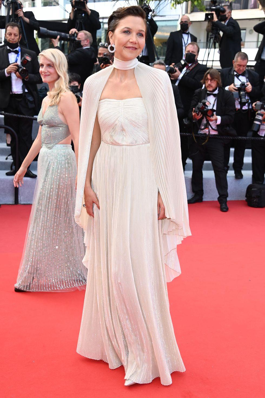 Maggie Gyllenhaal thanh lịch trong chiếc váy Celine màu nude phối thêm chiếc áo choàng xếp ly phù hợp. Để phù hợp với phong cách cổ điển, cô tinh tế làm tóc bob quyến rũ.