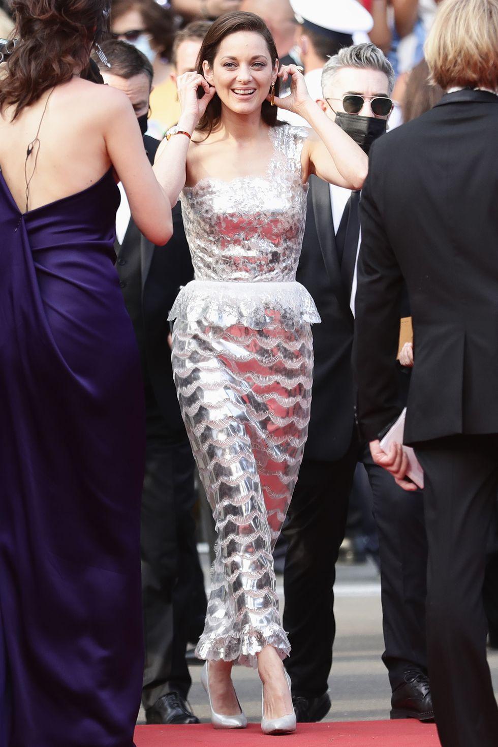 Ngôi sao Annette Marion Cotillard tỏa sáng trong chiếc váy Chanel bất đối xứng màu bạc ánh kim nổi bật. Cô nàng không quên phối thêm đôi giày cao gót đồng bộ, bông tai to bản… mang đến vẻ ngoài đơn giản nhưng không kém phần sang trọng
