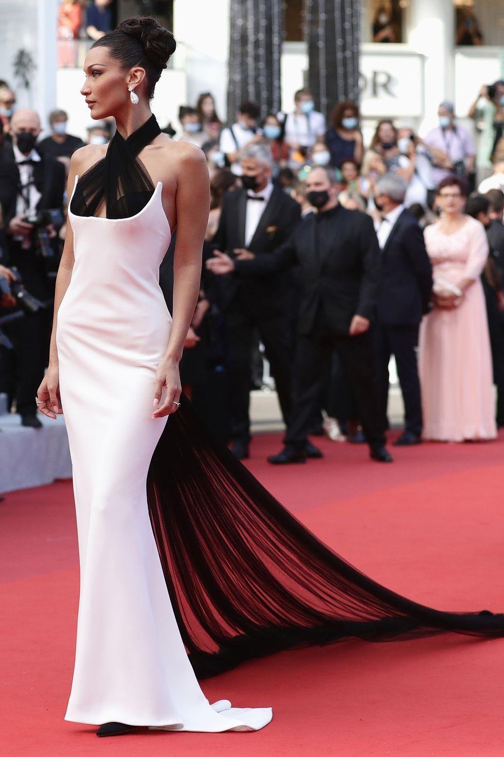 Bella Hadid tạo dáng ấn tượng trong chiếc váy hai dây cổ điển trong từ bộ sưu tập xuân hè 2002 của Jean Paul Gaultier. Chiếc váy liền thân màu trắng được tạo điểm nhấn bằng áo choàng vải tuyn đen và vạt áo phù hợp khoe trọn sắc vóc quyến rũ của cô.