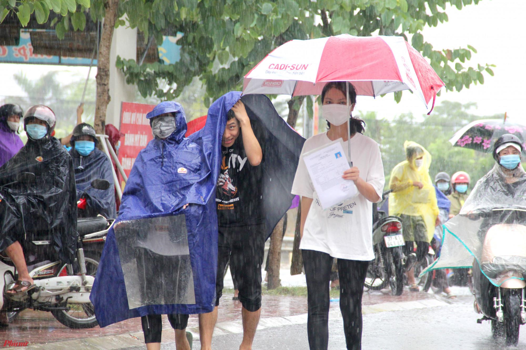 Cơn mưa lớn đầu buổi sáng khiến phụ huynh, thí sinh vất vả hơn trong việc di chuyển tới điểm thi