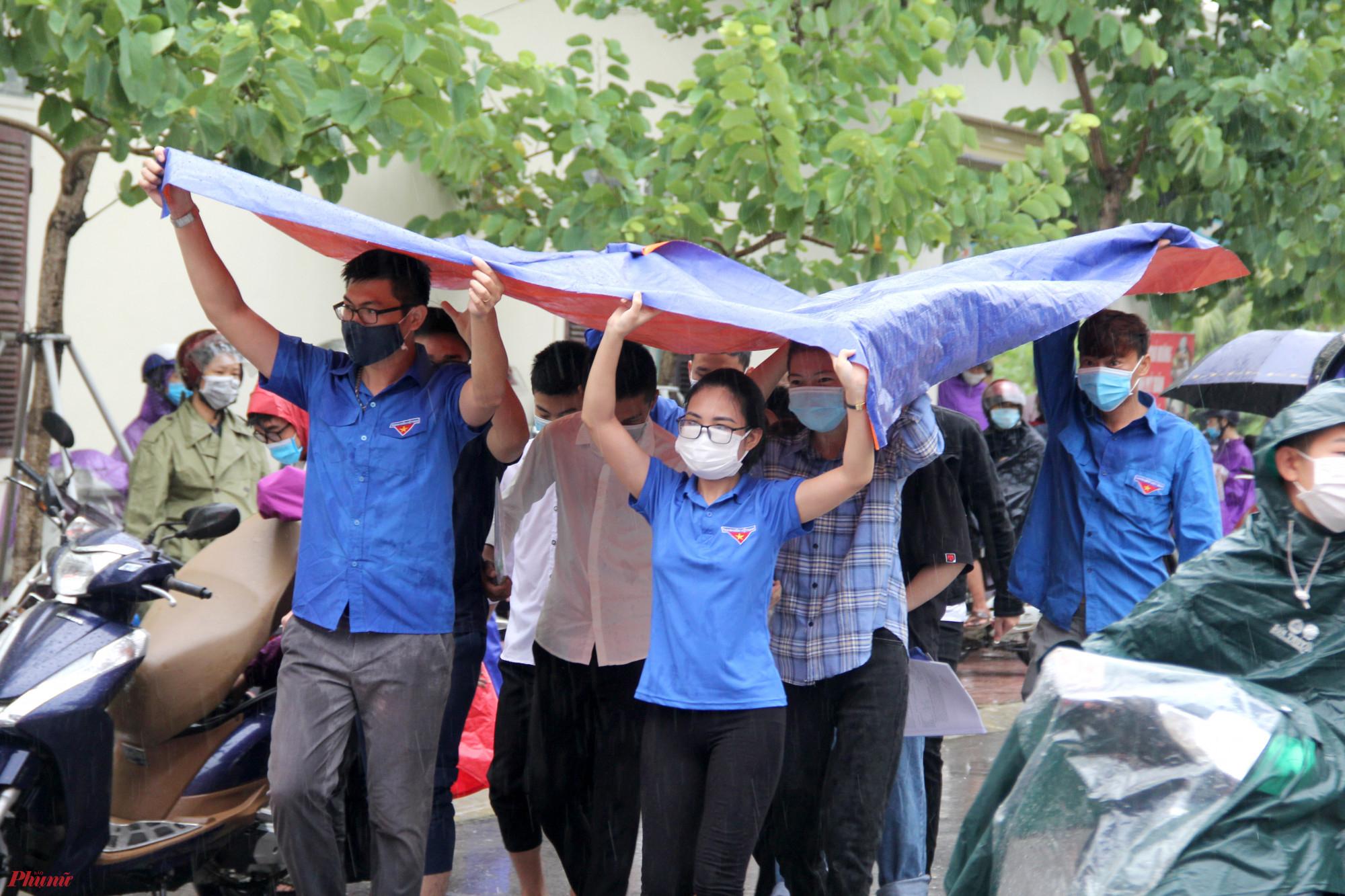 Tình nguyện viên dùng bạt lớn để che cho thí sinh đỡ ướt quần áo