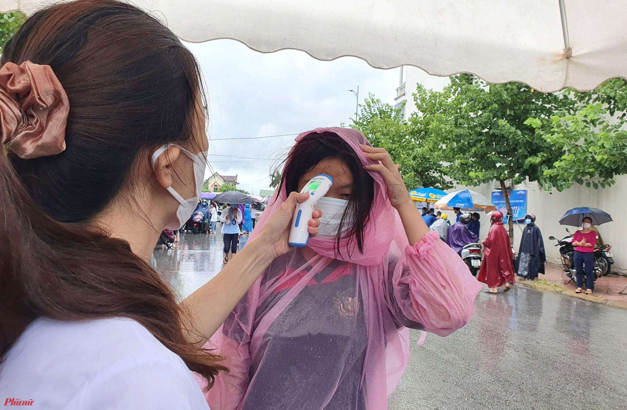 Dẫu mưa lớn, thí sinh vẫn được đo thân nhiệt, sát khuẩn tay trước khi vào điểm thi