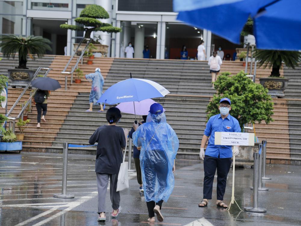 Tình nguyện viên che ô đón các thí sinh từ ngoài cổng trường.