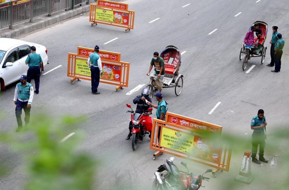 Các nhân viên cảnh sát kiểm tra người đi làm tại một trạm kiểm soát trong cuộc phong tỏa toàn quốc, ở thủ đô Dhaka, Bangladesh