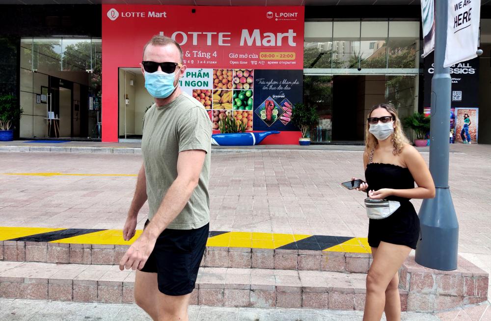 Hai du khách đang ở Nha Trang chấp hành mang khẩu trang ra đường để mua một số sản phẩm thiết yếu trong thời điểm giãn cách
