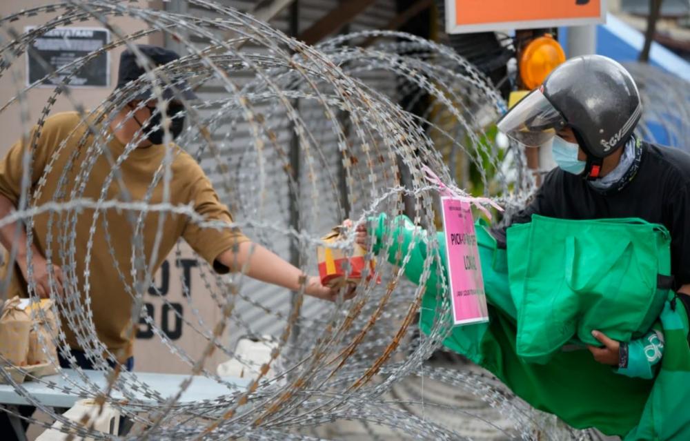 Một người dân (bên trái) nhận thức ăn từ người giao hàng qua hàng rào kẽm gai tại khu Segambut Dalam, ở Kuala Lumpur