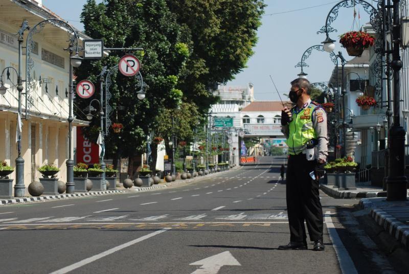 Một cảnh sát canh chừng trên con phố vắng ở Bandung, Indonesia hôm 4/7