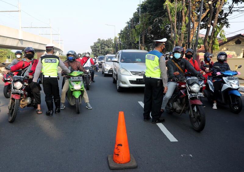 Người lái xe khi báo y tế tại một trạm kiểm soát ở Jakarta vào ngày 3/7/2021