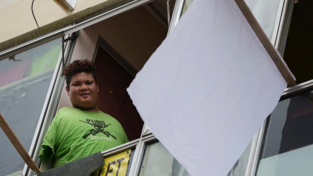 Mohamad Nor Abdullah, chàng trai khuyết tật sinh ra không có tay, cắm cờ trắng bên ngoài căn phòng do anh thuê ở Kuala Lumpur, Malaysia